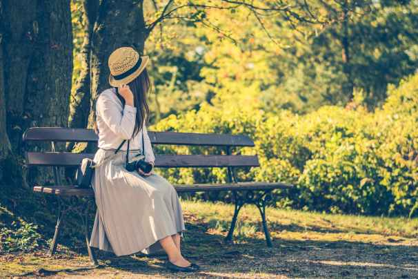 woman sitting on bench while looking on left side