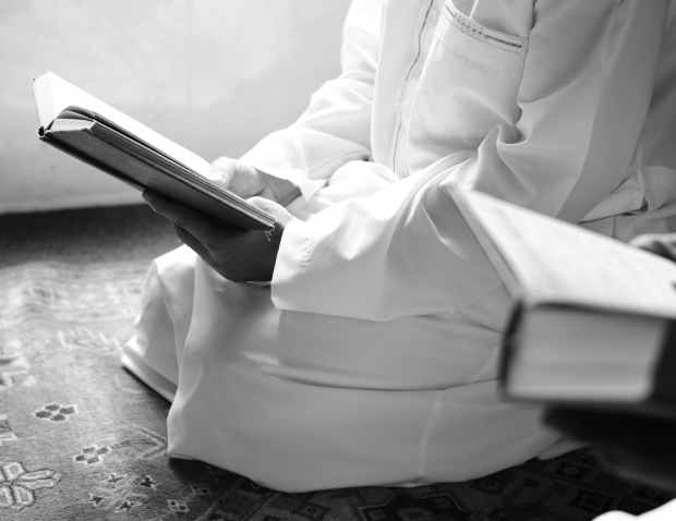 person kneeling holding book