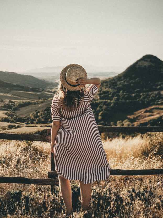 selective focus photography of woman holding brown straw hat