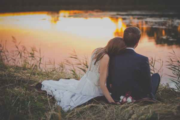 wedding couple sitting on green grass in front of body of water at sunset