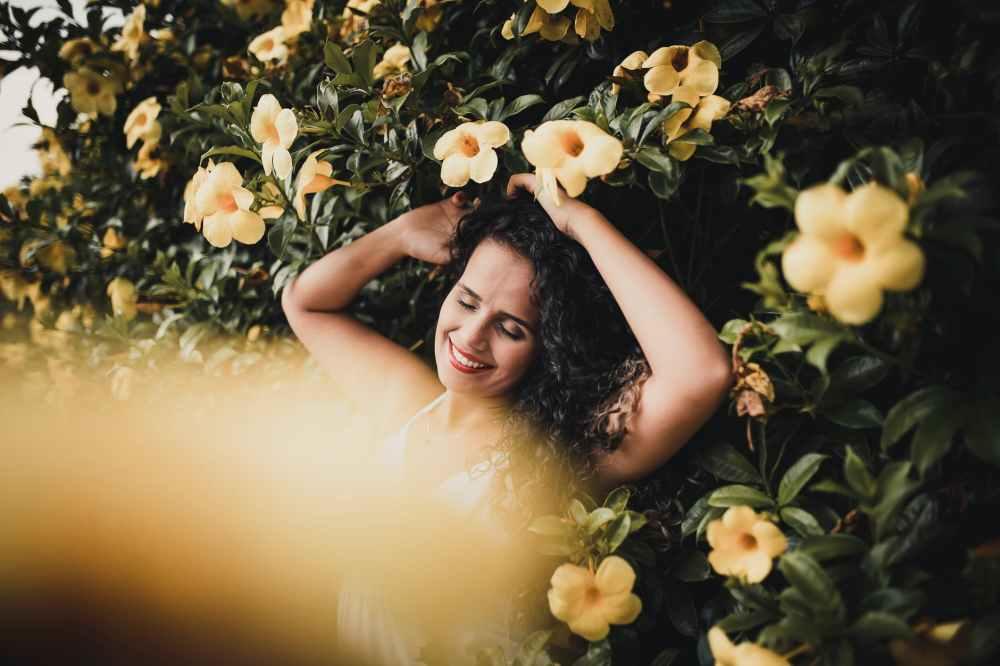 photo of woman standing near yellow flowers