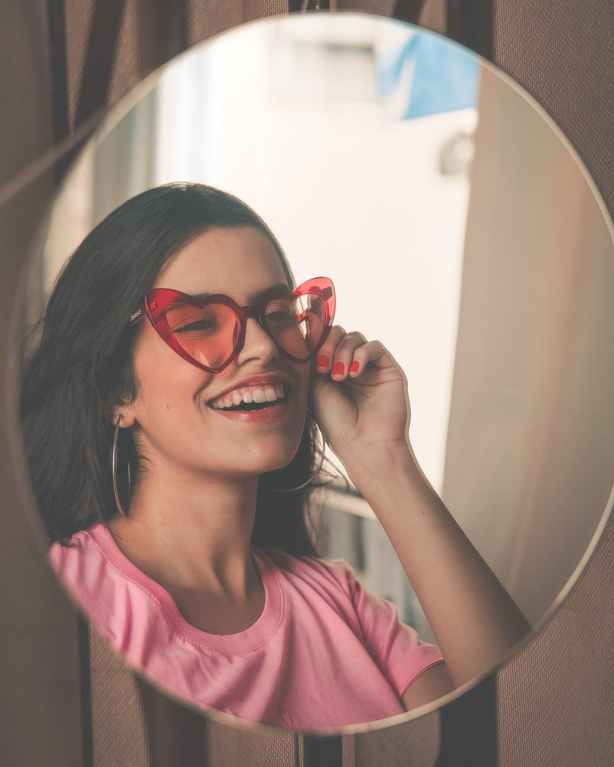 smiling woman wearing red sunglasses